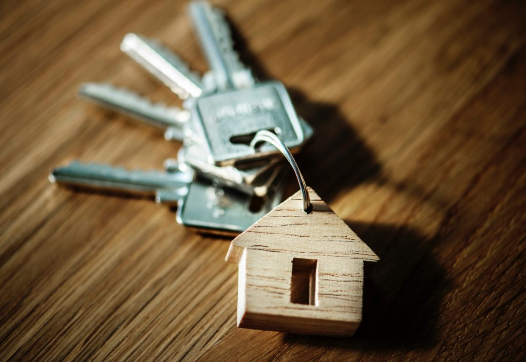 keys with wooden house keychain on table