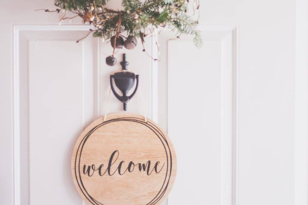 welcome sign hanging from white door